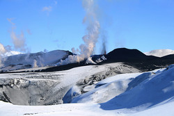white snow, black lava, steam and ash